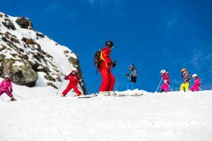 Glade skibørn lærer svingteknik af en engageret østrigsk skilærer.